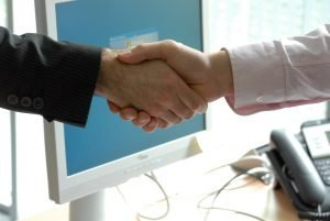 Shaking hands in front of computer screen